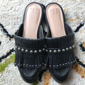 Black mules with studs and fringe